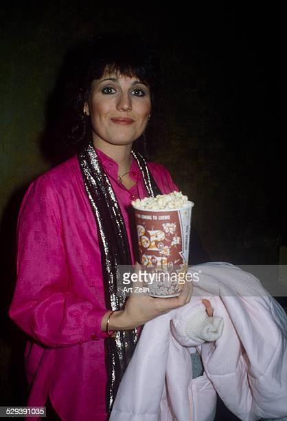 Lucie Arnaz with popcorn wearing a fuchsia blouse lame scarf carrying her coat circa 1970 New York