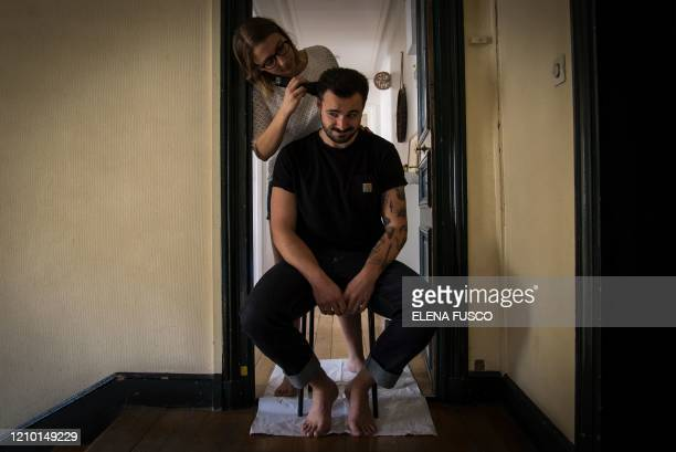 Lucie cuts the hair of her companion Pierre as he faces some haircut issues like many of people during lockdown in front of the door of their...