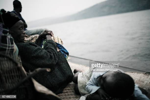 Lucie Malibua, age 68, wathes her granddaughter Sarah, age 5, as she tries to sleep while traveling on a boat made of big trees on the Congo River on...