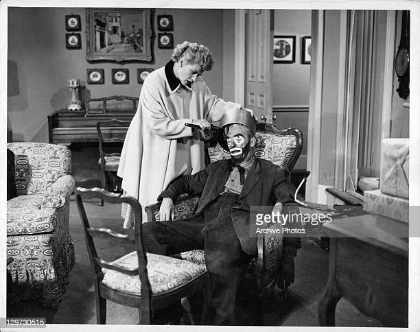 Lucille Ball putting pot on the head of unidentified man in the television series 'I Love Lucy', 1951.