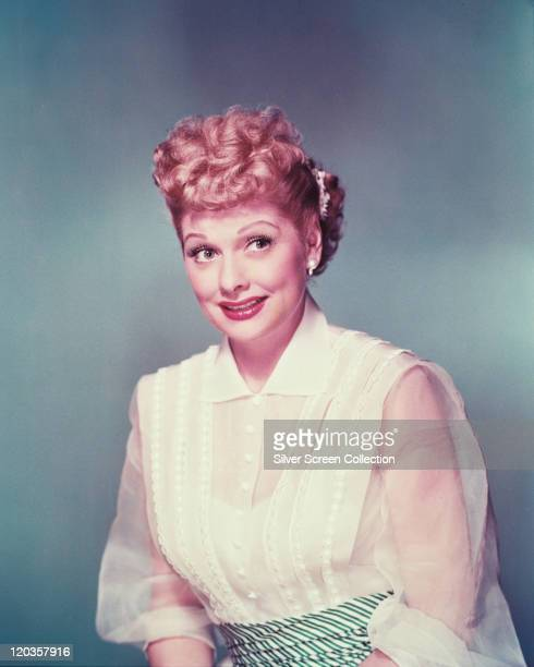 Lucille Ball US actress and comedian wearing a white blouse with white chiffon sleeves in a studio portrait against a grey background circa 1955