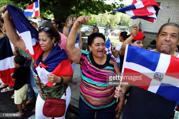Lucinda Gonzalez, center, waves the Dominican Republic flag during the Dominican Festival and Parade that marched through the streets of Jamaica...