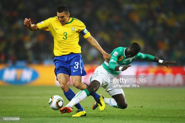 Lucio of Brazil and Ismael Tiote of Ivory Coast battle for the ball during the 2010 FIFA World Cup South Africa Group G match between Brazil and...