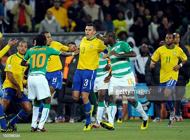 Lucio of Brazil is held back while engaged in an arguement with Gervinho of the Ivory Coast during the 2010 FIFA World Cup South Africa Group G match...