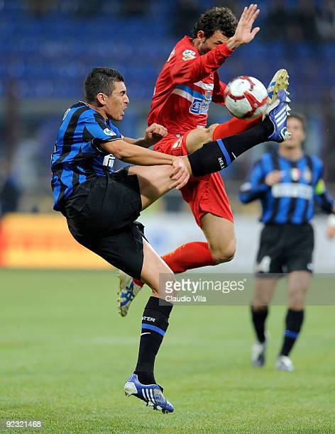 Lucio of FC Internazionale Milano competes for the ball with Gennaro Delvecchio of Catania Calcio during the Serie A match between Inter Milan and...