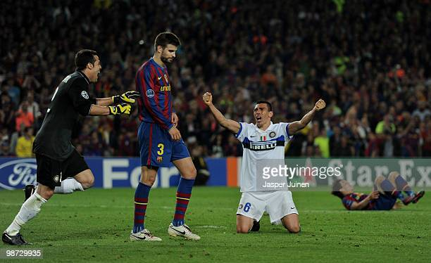 Lucio of Inter Milan on his knees celebrating as Gerard Pique of FC Barcelona trudges off the pitch dejected at the end of the UEFA Champions League...