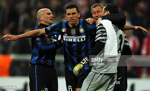 Lucio of Milan celebrates with team mates Esteban Cambiasso and goalkeeper Julio Cesar after winning the UEFA Champions League round of 16 second leg...