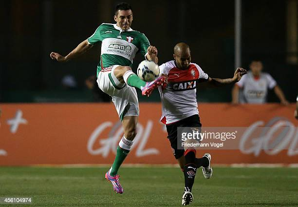 Lucio of Palmeiras fights for the ball with Dinei of Vitoria during the match between Palmeiras and Vitoria for the Brazilian Series A 2014 at...