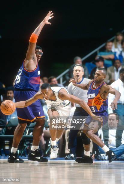 Lucious Harris of the Dallas Mavericks dribbles the ball between Frank Johnson and Oliver Miller of the Phoenix Suns during an NBA basketball game...
