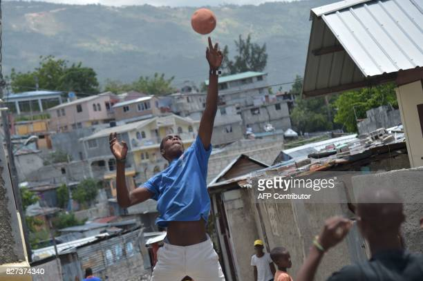 TOPSHOT Luckson Samedi plays a basketball game in the streets of Nezon in the haitian capital of Haiti PortauPrince on July 1 2017 Luckson with other...