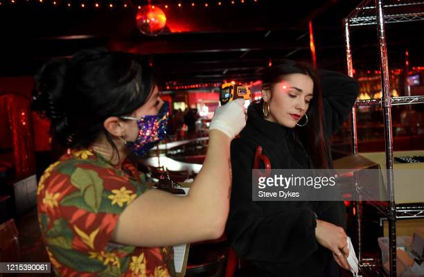 Lucky Devil dancer manager Staci checks the temperature of dancer Lou before she heads out for deliveries on March 27 2020 in Portland Oregon The...