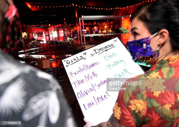 Lucky Devil dancer manager Staci goes over a list of dancers and drivers with owner Shon Boulden before they head out for deliveries on March 27 2020...