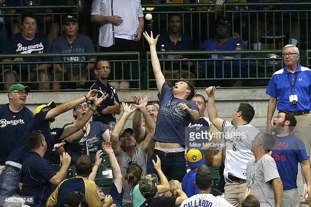 A lucky fan makes the jumping grab during the fifth inning of the game between the Pittsburgh Pirates and the Milwaukee Brewers at Miller Park on...