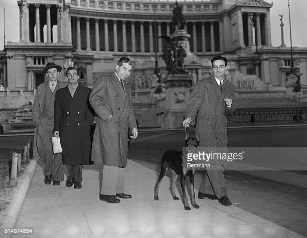 Lucky Luciano walking past the King Victor Emmanuel monuments home of the unknown soldier Other men are unidentified