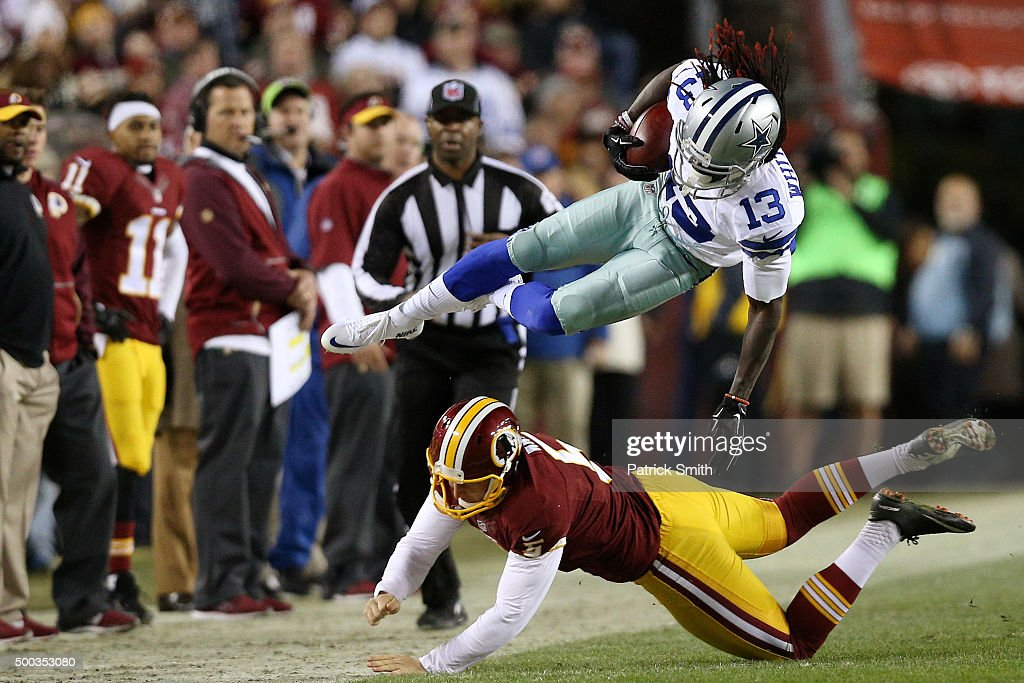 Lucky Whitehead #13 of the Dallas Cowboys is knocked out of bounds by punter Tress Way #5 of the Washington Redskins in the first quarter at FedExField on December 7, 2015 in Landover, Maryland.