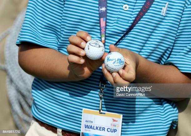 A lucky young spectator holds signed golf balls by Harry Ellis and Alfie Plant of the Great Britain and Ireland team during the morning foursomes...