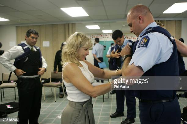 Lucy Adams fits the Stab Resistant Body Armour to Police Officer Warwick Lyes as it is handed out to the New Zealand Police Force December 19 2006 in...