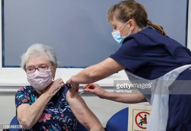 Lucy Airs receives a dose of AstraZeneca coronavirus disease vaccine from Ruth Davies, a practice nurse, at the Pentland Medical Practice on January...