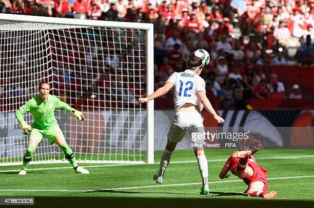 Lucy Bronze of England heads her team's winning goal past Erin McLeod of Canada during the FIFA Women's World Cup 2015 Quarter Final match between...