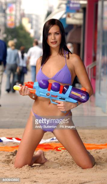 Lucy Clarkson poses on a man made beach during a photocall outside House of Fraser in London's Oxford Street to launch 'The Great Air Miles Giveaway'...