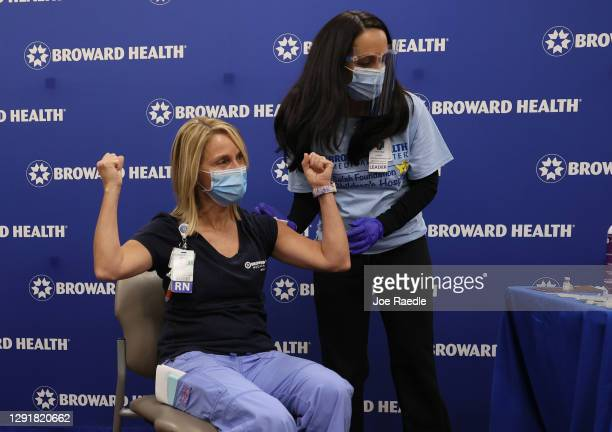 Lucy Corso, RN, Intensive Care Unit, Broward Health Medical Center, reacts after receiving a Pfizer-BioNtech COVID-19 vaccine from Kristina Castro,...