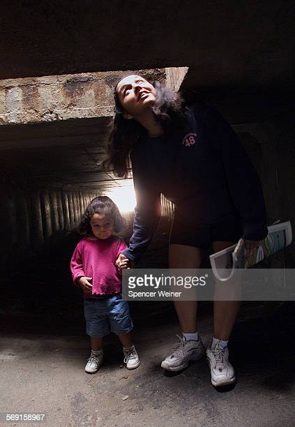 Lucy Escobar and her daughter Alicia rest half way under the 101 freeway in drain used for access to beach from la Conchita Profile of Ventura...