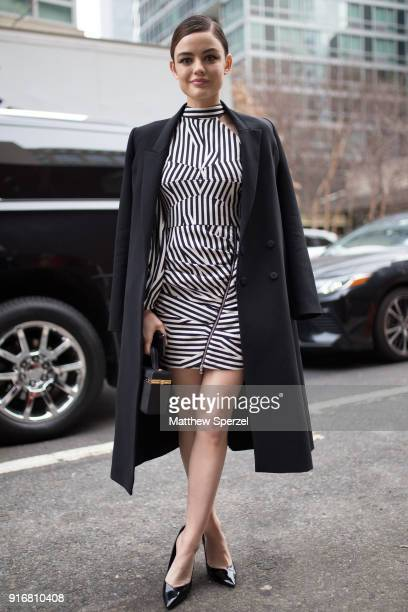 Lucy Hale is seen on the street attending SelfPortrait during New York Fashion Week wearing a black/white stripe dress with black long coat on...