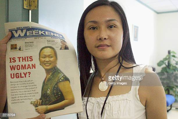 Lucy Hao a jewelry trader poses with her new nose and doubleeye lit next to a copy of the latest edition of Beijing weekend where she is featured on...
