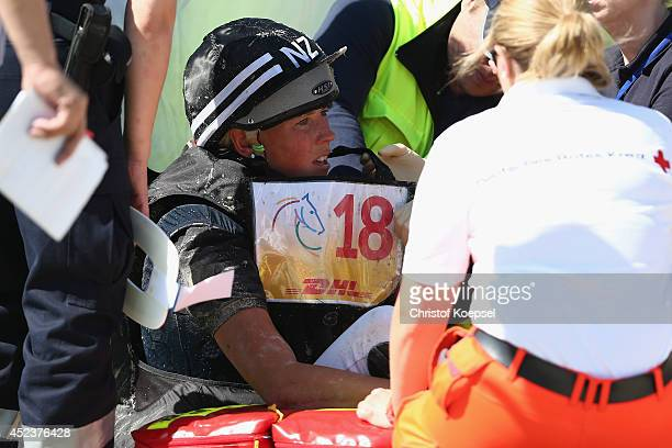 Lucy Jackson of New Zealand rides on Willy Do and is treated after falling down during the DHL Price Cross Country Test at Aachener Soers on July 19...