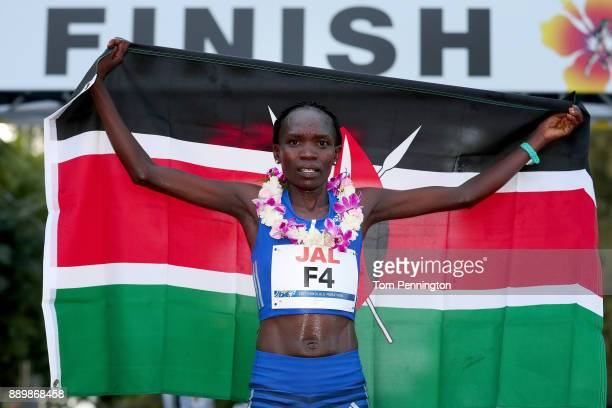 Lucy Karimi of Kenya poses with a flag after finishing second in the Women's division of the Honolulu Marathon 2017 on December 10 2017 in Honolulu...