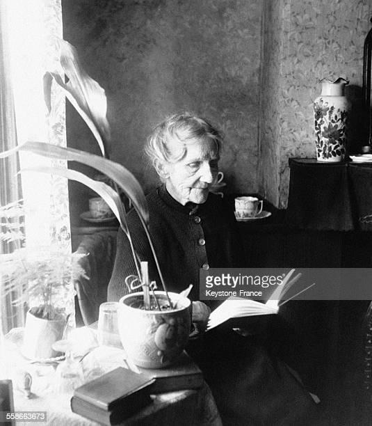 Lucy Webster une femme âgée lit un livre chez elle après les travaux de la journée au RoyaumeUni