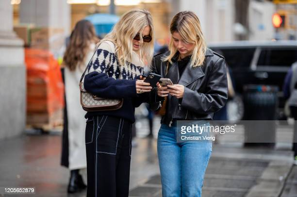 Lucy Williams and Sabina Socol texting on their smartphones is seen during New York Fashion Week Fall / Winter on February 11, 2020 in New York City.