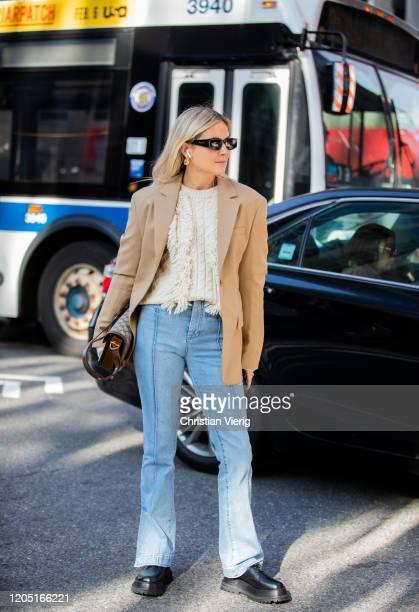 Lucy Williams is seen wearing beige blazer, knit, denim jeans outside Tory Burch during New York Fashion Week Fall / Winter on February 09, 2020 in...
