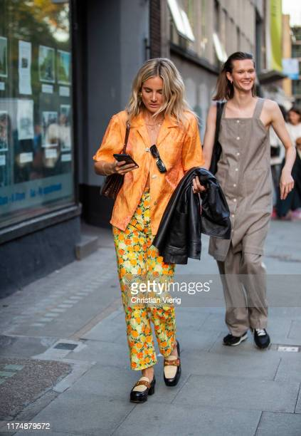 Lucy Williams is seen wearing orange button shirt, yellow pants with floral print outside Rejina Pyo during London Fashion Week September 2019 on...