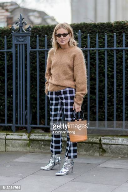 Lucy Williams wearing a beige knit bucket bag checked pants silver ankle boots outside Christopher Kane on day 4 of the London Fashion Week February...