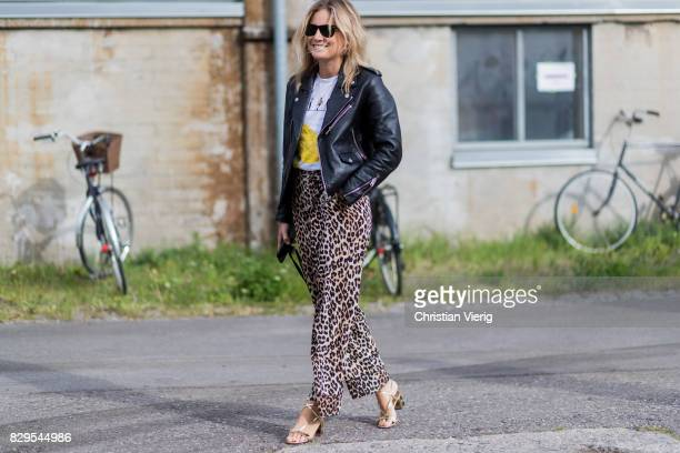Lucy Williams wearing pants with leopard print leather jacket outside Ganni on August 10 2017 in Copenhagen Denmark