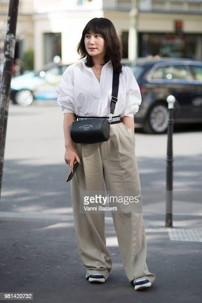Lucy Zhang poses wearing Celine pants Dior bag and Louis Vuitton sneakers after the Comme des Garcons show at the Pavillion Cambon during Paris...