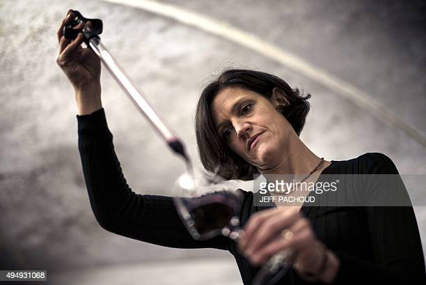 BOYET Ludivine Griveau the first female manager of the Hospices de Beaune poses with a glass of wine in the hospices' wine cellar in Beaune on...