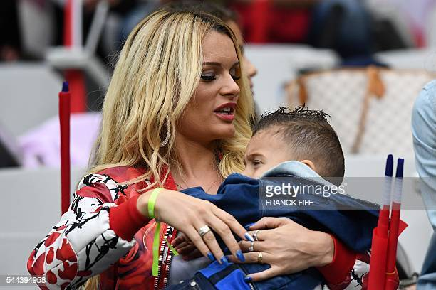 Ludivine Payet the wife of France's forward Dimitri Payet holds her son prior to the start of the Euro 2016 quarterfinal football match between...