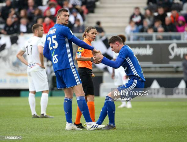 Ludovic Ajorque of Strasbourg and referee Stephanie Frappart first woman ro ref a Ligue 1 match help Anthony Caci of Strasbourg to get up during the...