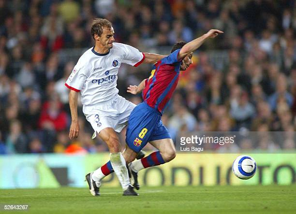 Ludovic Giuly of FC Barcelona and Mariano Pernia of Getafe is seen in action during the La Liga match between FC Barcelona and Getafe on April 17...
