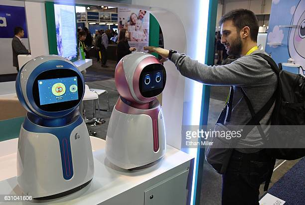 Ludovic Houchu looks at a prototype Kikoo autonomous robot for children made by Hanwuji Intelligence at CES 2017 at the Sands Expo and Convention...