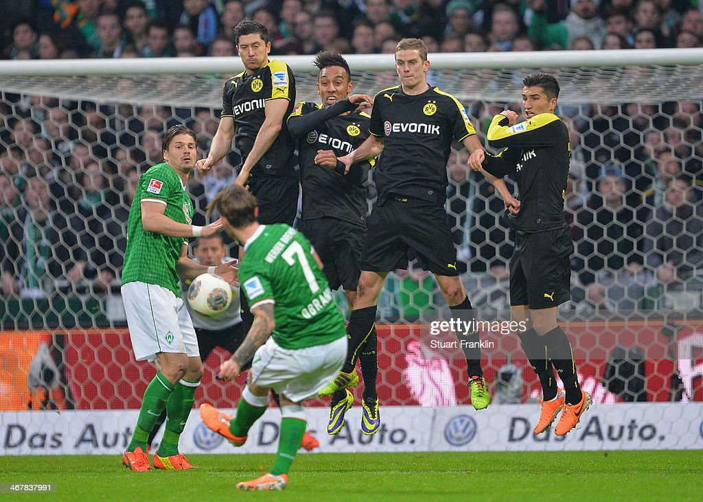 Ludovic Obraniak of Bremen takes a free kick against wall og Dortmund players during the Bundesliga match between Werder Bremen and Borussia Dortmund at Weserstadion on February 8, 2014 in Bremen, Germany.