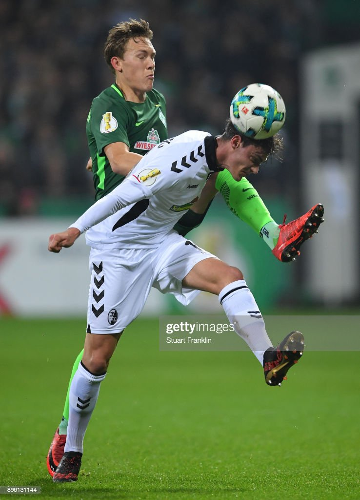 Ludwig Augustinsson of Bremen is challenged by Pascal Stenzel of Freiburg during the DFB Cup match between Werder Bremen and SC Freiburg at Weserstadion on December 20, 2017 in Bremen, Germany.