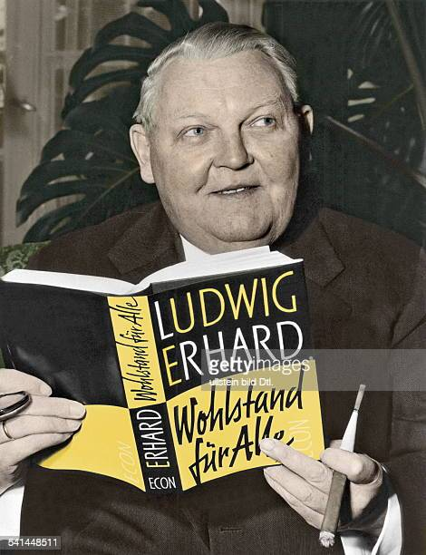 Ludwig Erhard German politician and minister of trade and commerce holding his book 'Prosperity for everybody' 1957 Picture colored later identical...