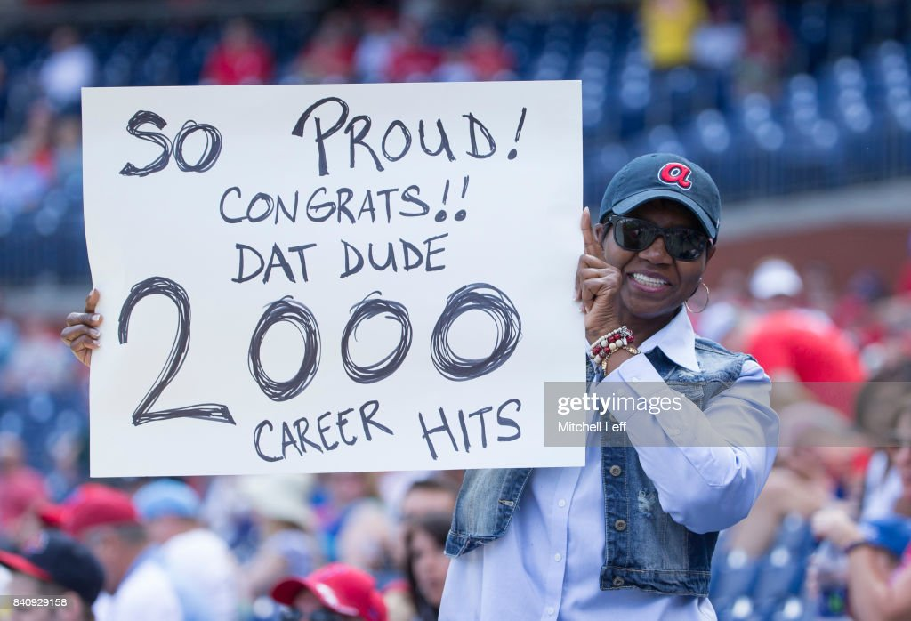 Lue Phillips, the mother of Brandon Phillips #4 of the Atlanta Braves (NOT PICTURED) holds up a sign congratulating her son for having 2,000 career hits during the game against the Philadelphia Phillies in game one of the doubleheader at Citizens Bank Park on August 30, 2017 in Philadelphia, Pennsylvania.