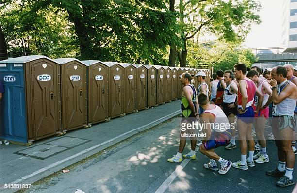 Läufer des Hamburger hanseMarathons 1992 stehen vor einer Reihe von nebeneinander aufgestellten Toilettenhäuschen Schlange Die blaubraunen Toiletten...