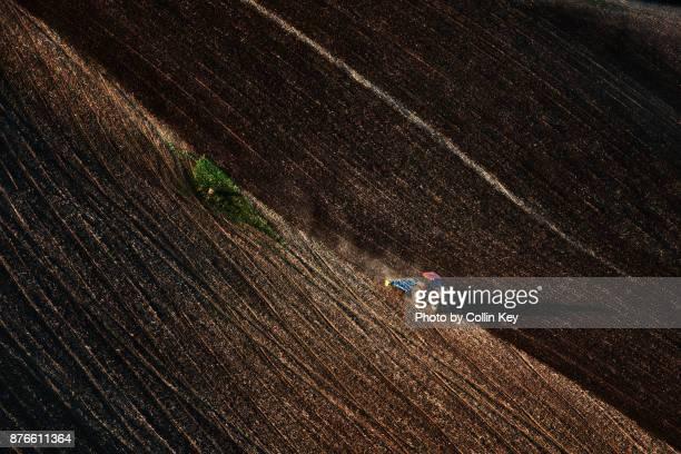 Luftaufnahme: braunes Feld und Traktor