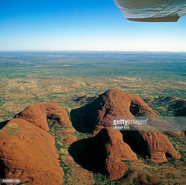 Luftaufnahme des roten Zentrums Australiens mit Blick auf die runden Felskoepfe der Olgas spektakulaere Reste eines praekambrischen Gebirges dahinter...