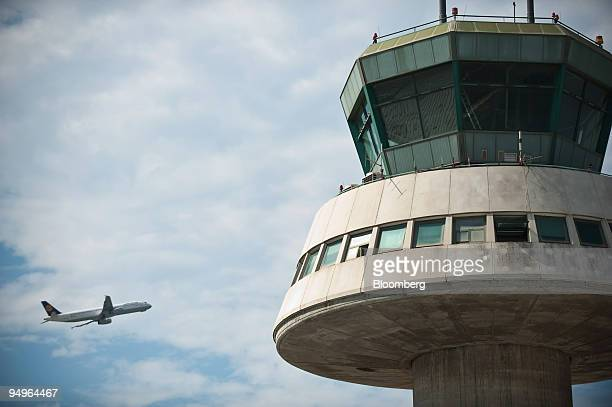 Lufthansa airplane flies behind the control tower at the El Prat International Airport in Barcelona Spain on Tuesday June 30 2009 A new Terminal 1...